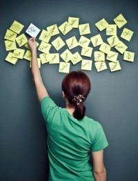 A woman arranging topics on post-it notes attached to a board