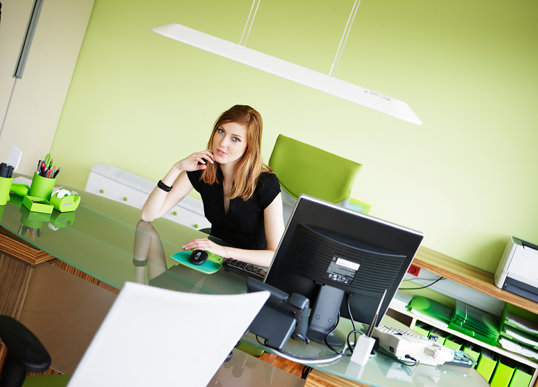 Potential WordPress user sitting at her PC in a green room